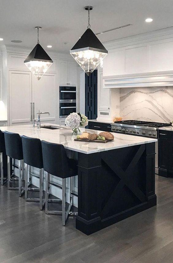 una cucina contemporanea con armadi neri, top in pietra bianca e alzatina abbinata e lampade accattivanti