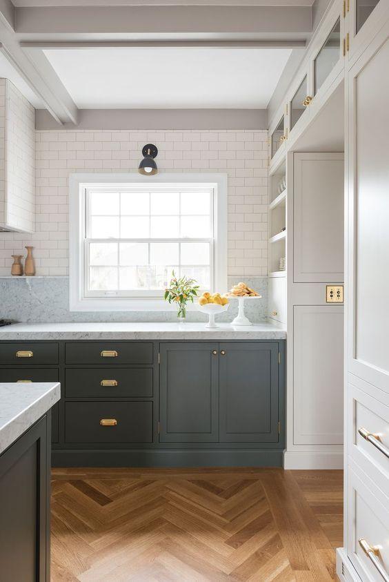 una cucina grigio grafite con piani in pietra neutra e armadi superiori neutri più eleganti hardware in ottone