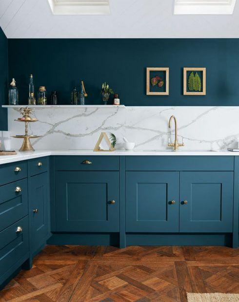 una cucina verde acqua chic ed elegante con piani in pietra bianca e un backsplash abbinato più tocchi d'oro