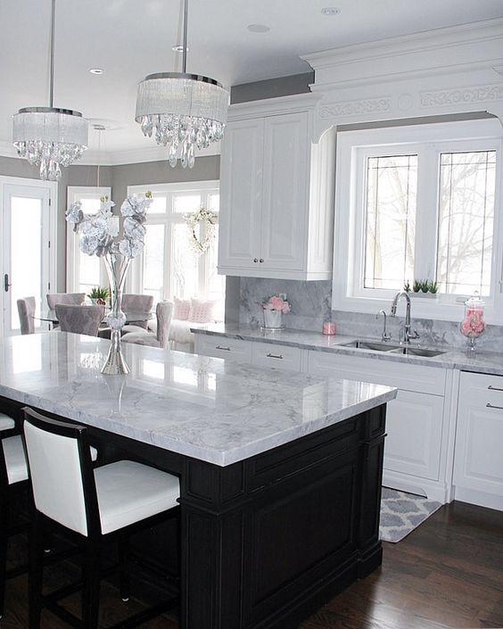 un'isola da cucina nera e cabine bianche sono coperte con gli stessi piani di lavoro in pietra neutra per un aspetto coeso