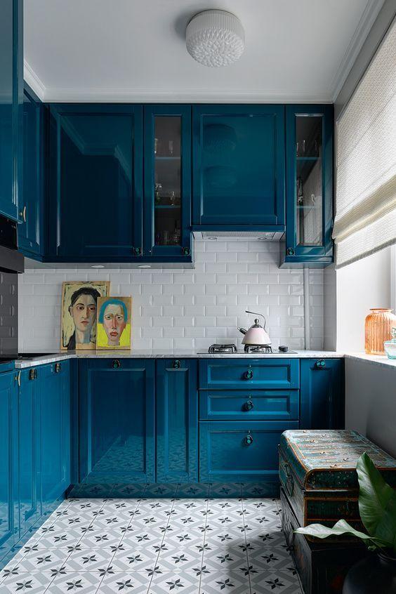 una cucina blu brillante con un piani di lavoro in pietra bianca e un backsplash in piastrelle bianche della metropolitana per un aspetto altamente contrastante