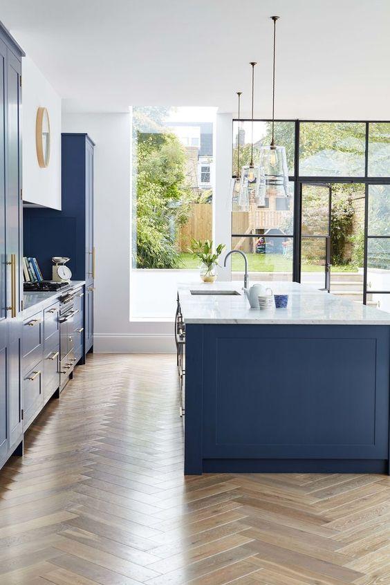 una cucina blu luminosa e fresca con piani in pietra bianca e hardware in ottone sembra molto chic