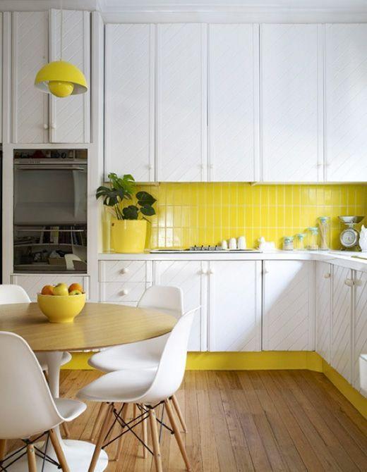 una cucina con accenti giallo limone con armadi bianchi e un backsplash di piastrelle gialle che riecheggia accenti e tocchi luminosi