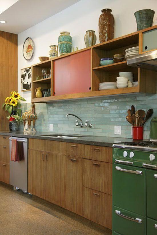 una luminosa cucina moderna della metà del secolo con tocchi rossi e verdi e piastrelle magre verde menta sul backsplash