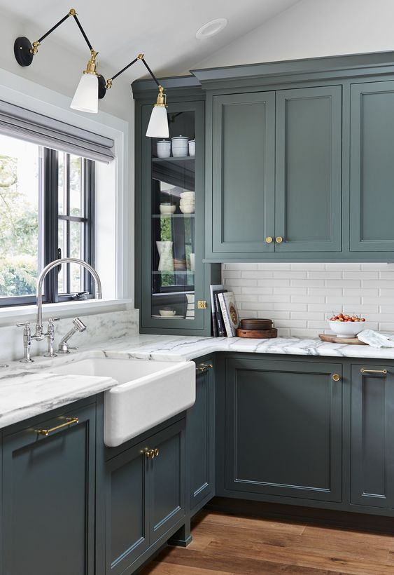un'elegante cucina vintage verde con piastrelle bianche magre e ripiani in marmo per un look più raffinato ed elegante