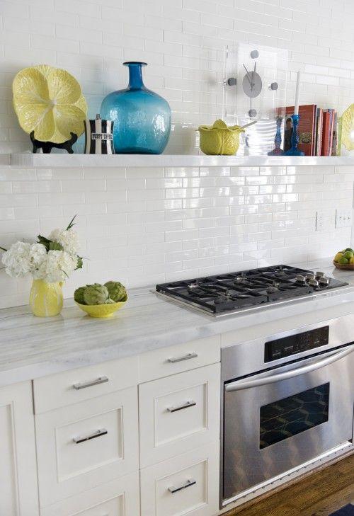 un'elegante cucina moderna da fattoria con ripiani in pietra e piastrelle bianche magre sul backsplash che brilla un po '