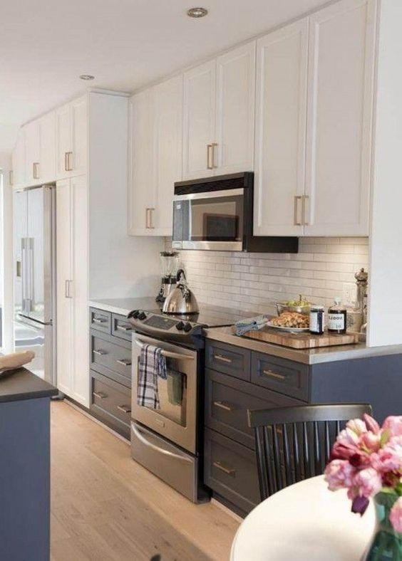 una cucina bicolore in blu scuro e bianco con un backsplash in piastrelle bianche e ripiani in metallo per un look luminoso e chic