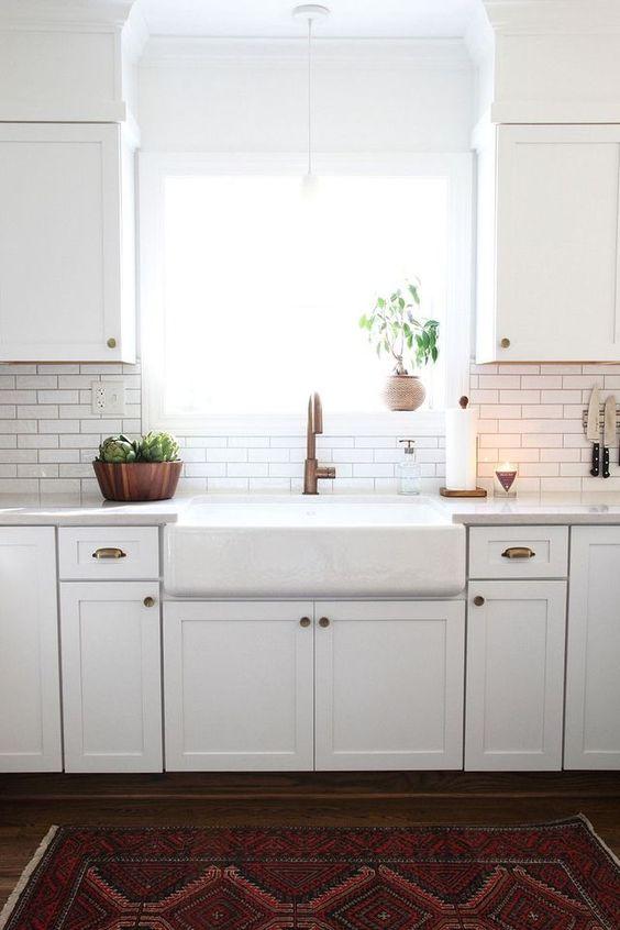una moderna cucina bianca da fattoria con piastrelle bianche sottili e stucco nero sul backsplash e tocchi di rame qua e là