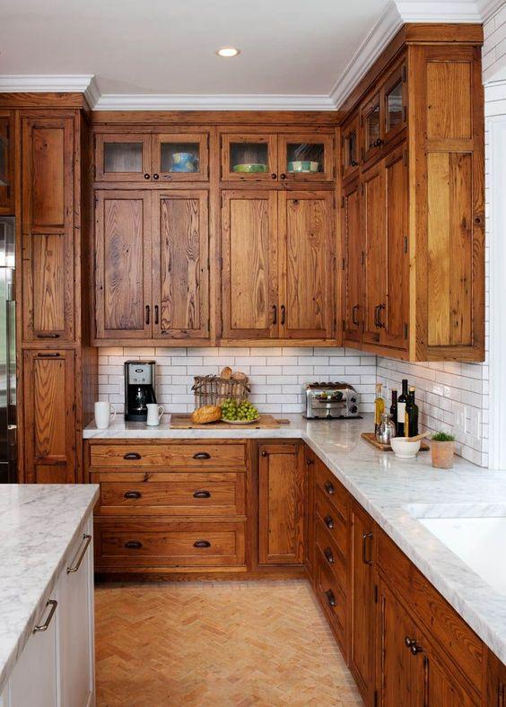una cucina rustica con armadi dalle tinte calde, piastrelle bianche e sottili, ripiani in stoen bianchi e maniglie vintage