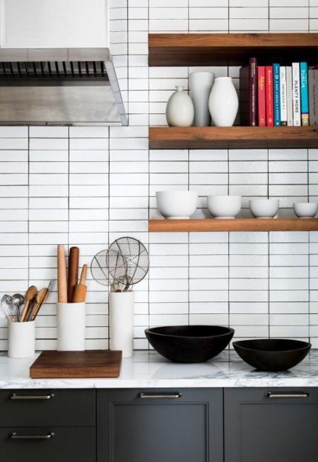 piastrelle bianche sottili accentate con malta nera evidenziano lo stile contemporaneo della cucina