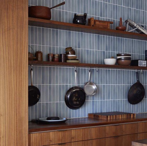 armadi in legno dai toni caldi abbinati a un backsplash di piastrelle skinny azzurro sembrano contrastanti e rinfrescati
