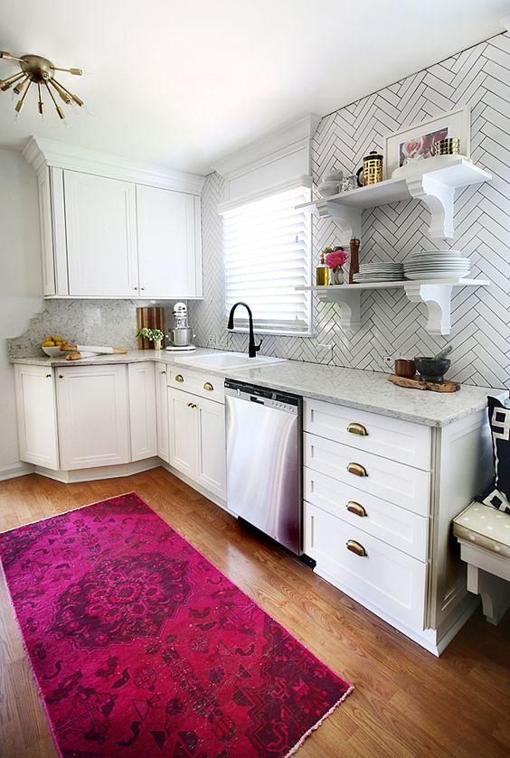 una cucina bianca contemporanea con ripiani in pietra e piastrelle bianche sottili evidenziate con malta nera sembra molto bella