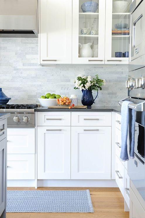Armadi bianchi moderni, piano grigi e piastrelle skinny in marmo grigio sul backsplash per una cucina neutra e accogliente