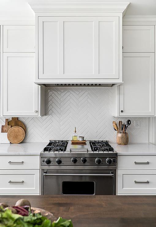 le piastrelle bianche e magre rivestite a spina di pesce si abbinano agli armadi e aggiungono interesse al modello in cucina
