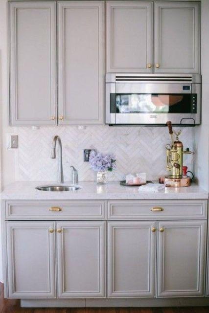 mobili da cucina vintage grigi e piastrelle skinny in marmo fatte con un motivo a chevron per più accattivante