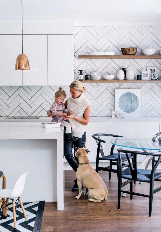 le lunghe piastrelle bianche e magre evidenziate con malta nera aggiungono motivo alla cucina neutra e la rendono più accattivante