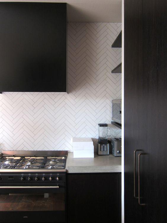 una cucina minimalista scura fatta con ripiani in cemento e piastrelle bianche e magre rivestite con un motivo a chevron per un look accattivante
