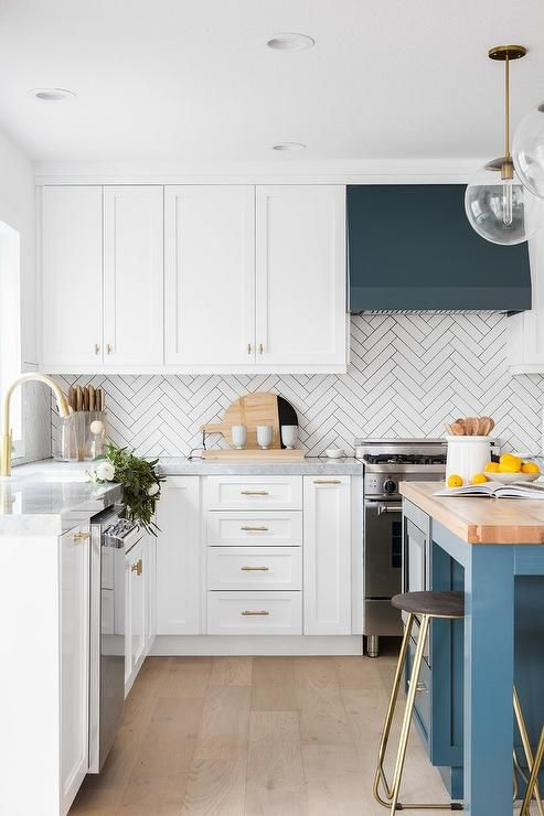 una splendida cucina moderna con accenti verde acqua e blu, piano del tavolo butchblock e un backsplash in piastrelle bianche con motivo a chevron