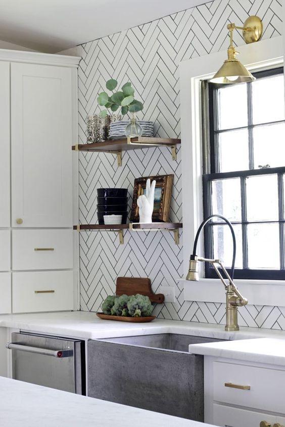 piastrelle bianche sottili con stucco nero evidenziano lo stile moderno della cucina e si aggiungono allo spazio neutro