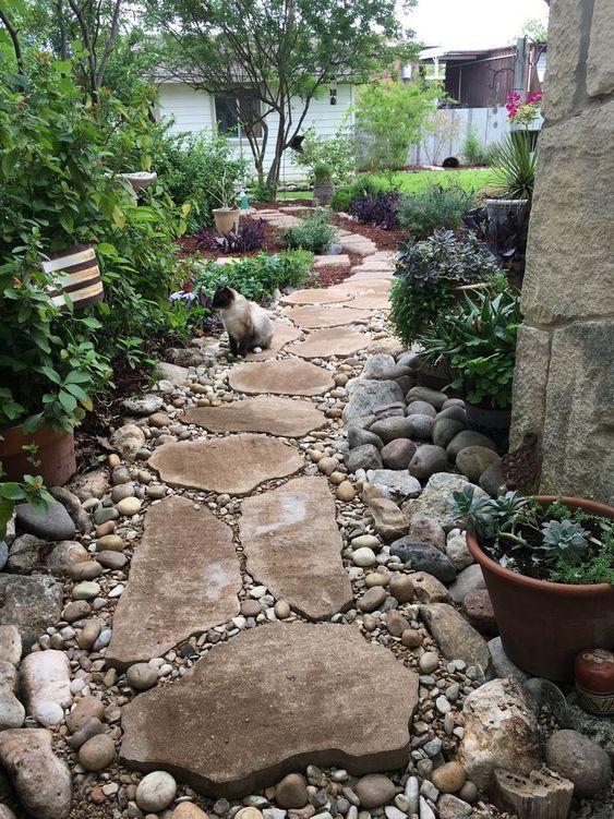 un sentiero del giardino naturale e rustico di pietre più grandi e ciottoli più piccoli intorno sembra fresco e chic
