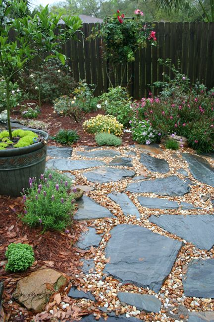camminamento del giardino rilassato e tutto naturale con ciottoli e pietre scure ruvide di varie forme e sguardi