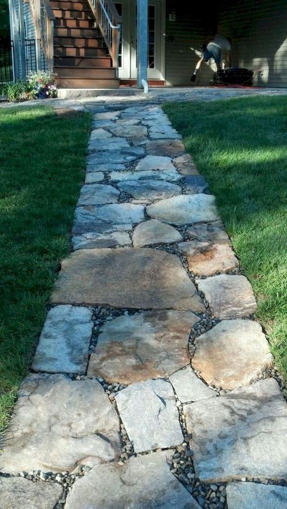 camminamento da giardino in pietra grezza con piccoli ciottoli in mezzo è un'idea elegante e molto semplice