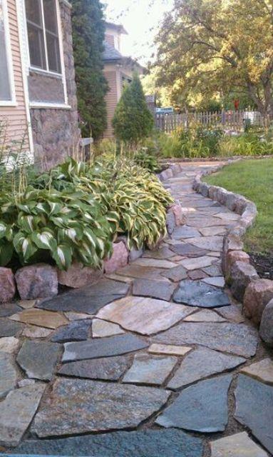 un elegante vialetto da giardino in pietra grezza con un bordo alto sembra elegante e molto materico