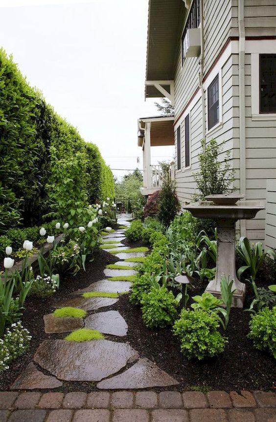 vialetto giardino in pietra zen con pezzi scuri e ruvidi e muschio luminoso che cresce nel mezzo