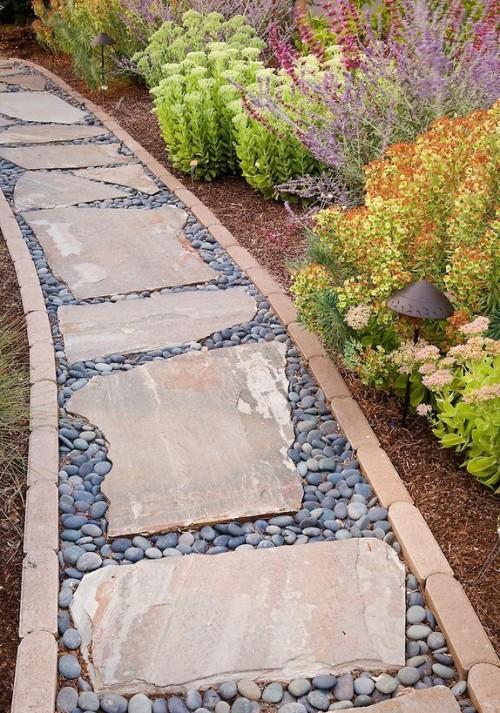un insolito sentiero del giardino fatto di ciottoli e pietre grezze più un bordo coordinato sembra accurato anche se non troppo