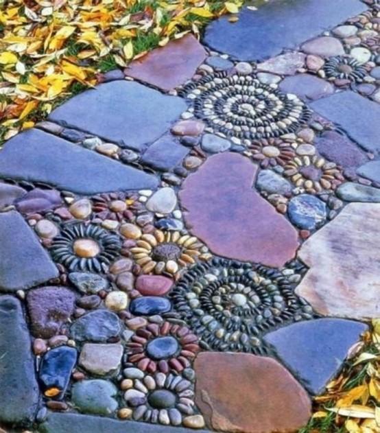 un audace camminamento del giardino con pietre di colore tenue e ciottoli che formano motivi floreali e vortici sembra molto accattivante