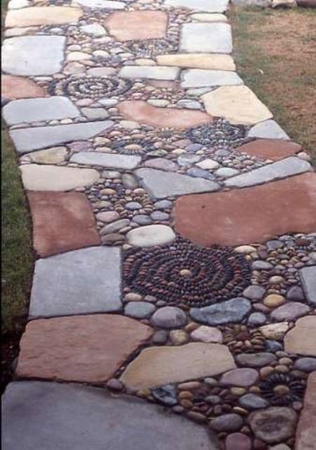 camminamento giardino audace e unico di pietre di colore tenue e ciottoli che formano motivi floreali