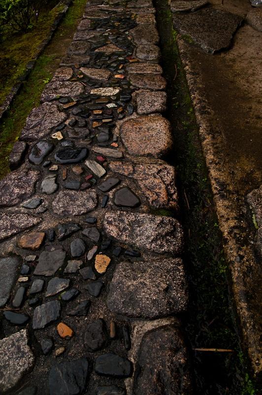 un camminamento da giardino in pietra grezzo e rilassato di pietre grandi e più piccole e più scure al centro del percorso