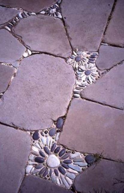 un sentiero in pietra grezza con inserti di piccoli fiori di ciottoli che lo rendono più audace e più carino