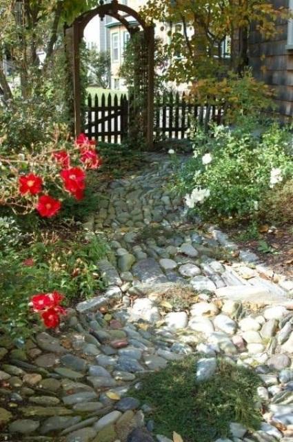 un camminamento da giardino in pietra di pietre di colore tenue che formano uno schema caotico si adatterà a un giardino segreto o di ispirazione fiabesca