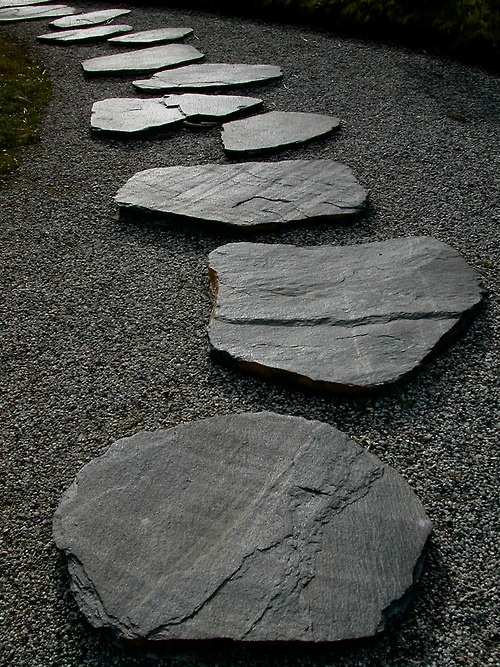 ghiaia grigia e grandi pietre grezze per un percorso costituiscono un vialetto fresco e audace con un'atmosfera zen