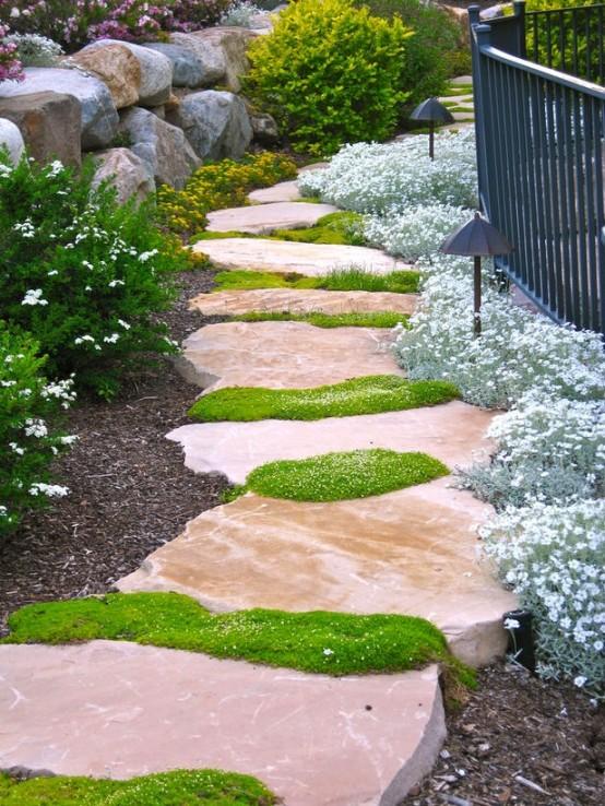 un bel camminamento in pietra rosa con muschio verde che cresce nel mezzo è un tocco chic e luminoso per il tuo spazio esterno