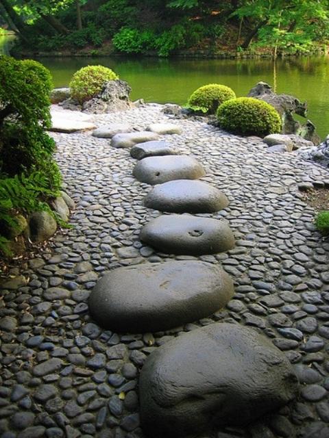 pietre più piccole e pietre più grandi appiattite in cima si adattano a un giardino zen con molta vegetazione