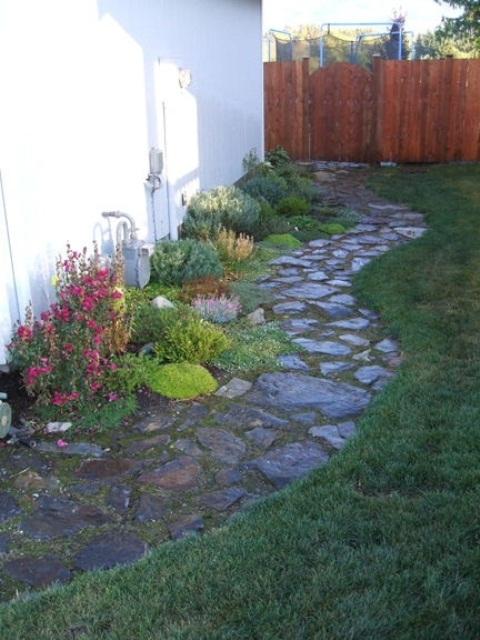 un sentiero in pietra da giardino con muschio in mezzo e fiori luminosi che crescono accanto ad esso