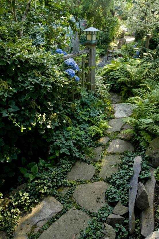 un rilassante sentiero del giardino in pietra con vegetazione in mezzo e fogliame lussureggiante che cresce intorno per un aspetto rilassante
