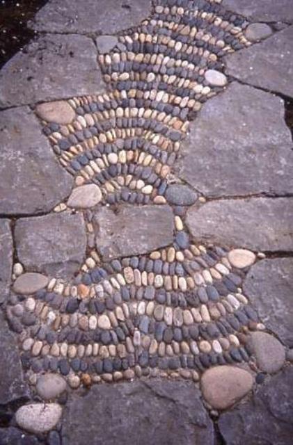 un vialetto da giardino in pietra e ciottoli con ciottoli che formano alcuni motivi sembra fresco e audace