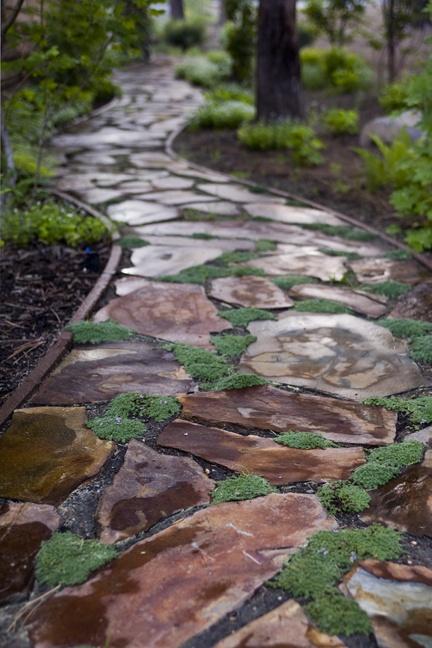 camminamento giardino in pietra grezza con muschio e bordi accurati per un'atmosfera naturale ma curata