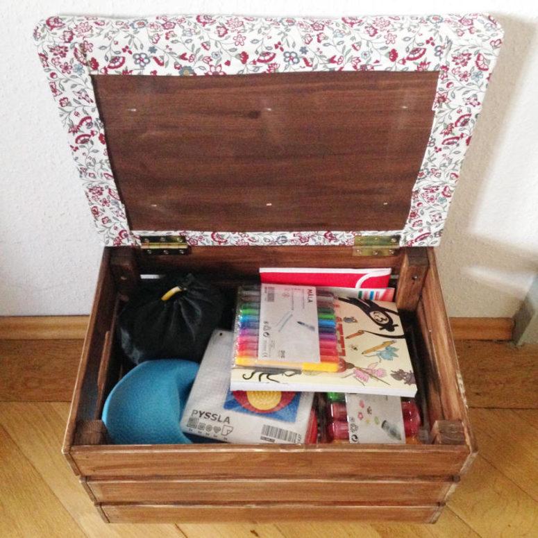un semplice e piccolo pouf di una scatola IKEA Knagglig con un piano ricoperto di tessuto floreale luminoso e un contenitore all'interno