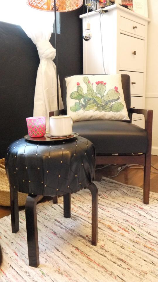 uno sgabello IKEA Frosta si è trasformato in un piccolo pouf chic rivestito in pelle nera con un tocco lucido