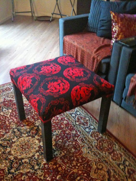 un tavolo IKEA Lack rinnovato con un tessuto stampato nero e rosso brillante sulla parte superiore da utilizzare come poggiapiedi o pouf