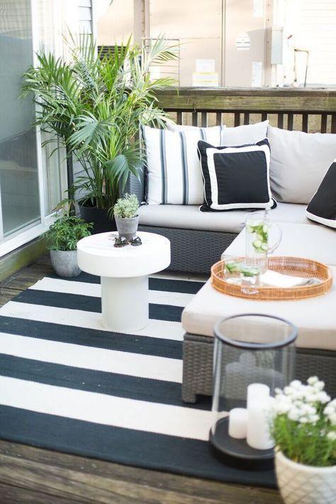 un piccolo terrazzo bianco e nero con una panca imbottita a forma di L, un tavolino da caffè, una lanterna a candela e piante in vaso