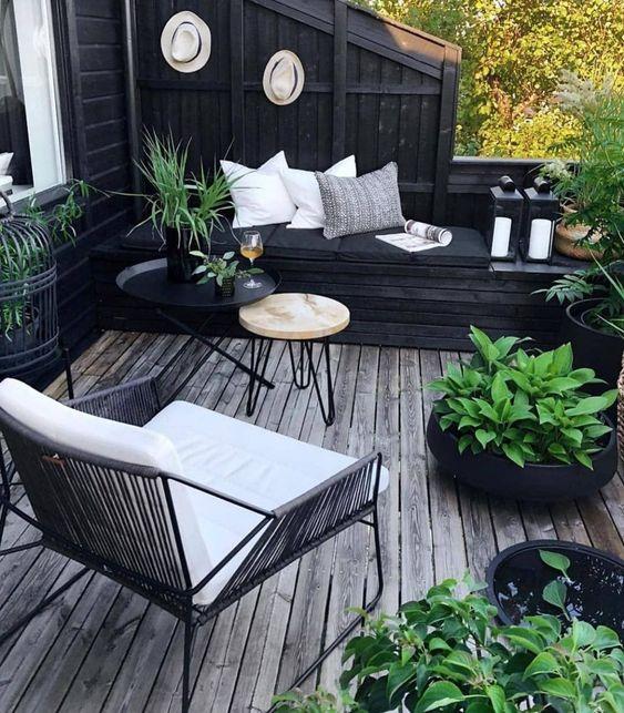 un piccolo terrazzo bianco e nero di ispirazione boho con mobili moderni, cuscini, vegetazione in vaso per rinfrescare lo spazio