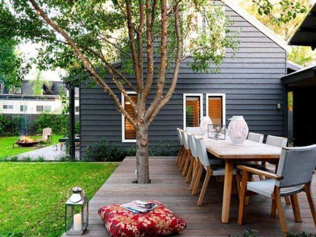 un piccolo terrazzo trasformato in uno spazio da pranzo, con mobili moderni, un albero vivente, una lanterna a candela e cuscini