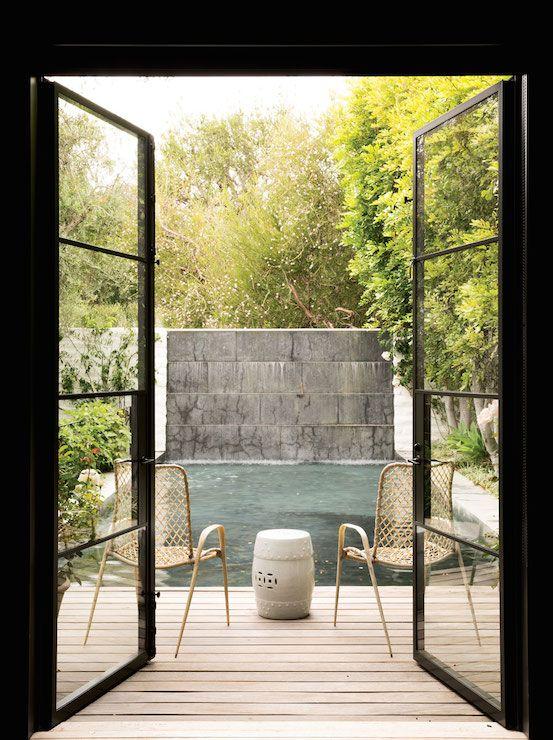 un piccolo terrazzo con un paio di sedie in rattan e un elegante tavolino da caffè in stile boho di fronte alla piscina