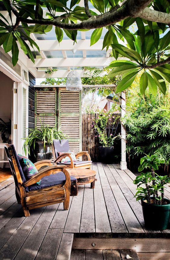 un piccolo terrazzo con un paio di sedie in legno stravaganti, un tavolino e un po 'di verde in vaso per un'atmosfera accogliente