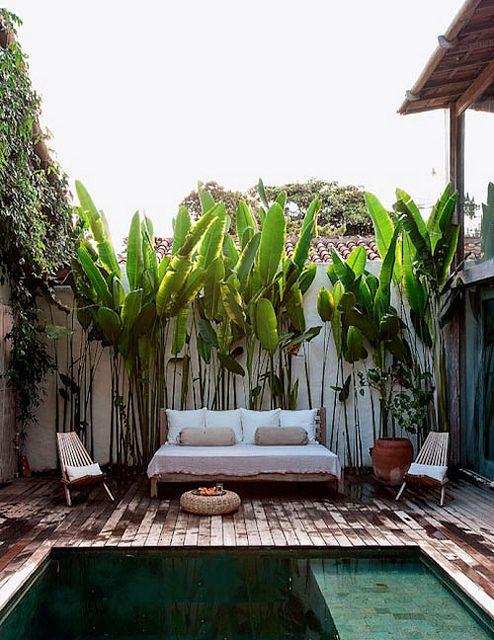 un piccolo terrazzo con un comodo divano letto, alcune sedie pieghevoli, un pouf in iuta e verde